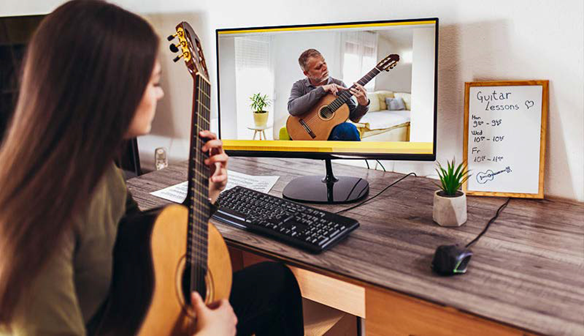 Student getting virtual guitar lessons | AVIXA