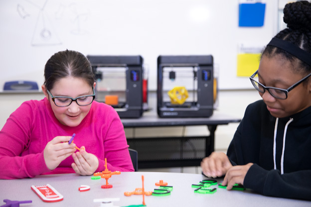 Students playing with 3D printers | AVIXA