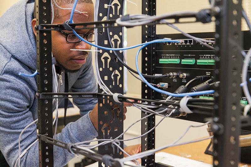 Man looking at installation cables | AVIXA